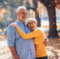 An older couple hugging and laughing while having fun outdoors after seeing their Delta Dental dentist in Castle Hills