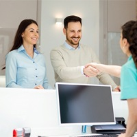 A man and woman shaking hands with the dental receptionist upon their arrival