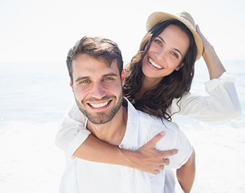 young couple on beach smiling after getting teeth whitening in San Antonio