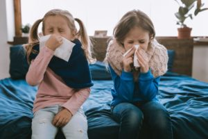 two little girls sitting on a bed and blowing their noses